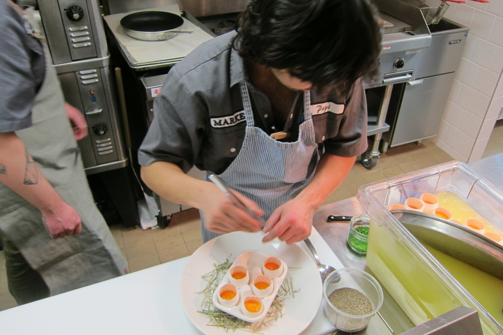 Chef Daniel Ramon preparing Market Eggs.  Yolks gently poached in their own shells and topped with a delicate Scallion Chantilly Cream.