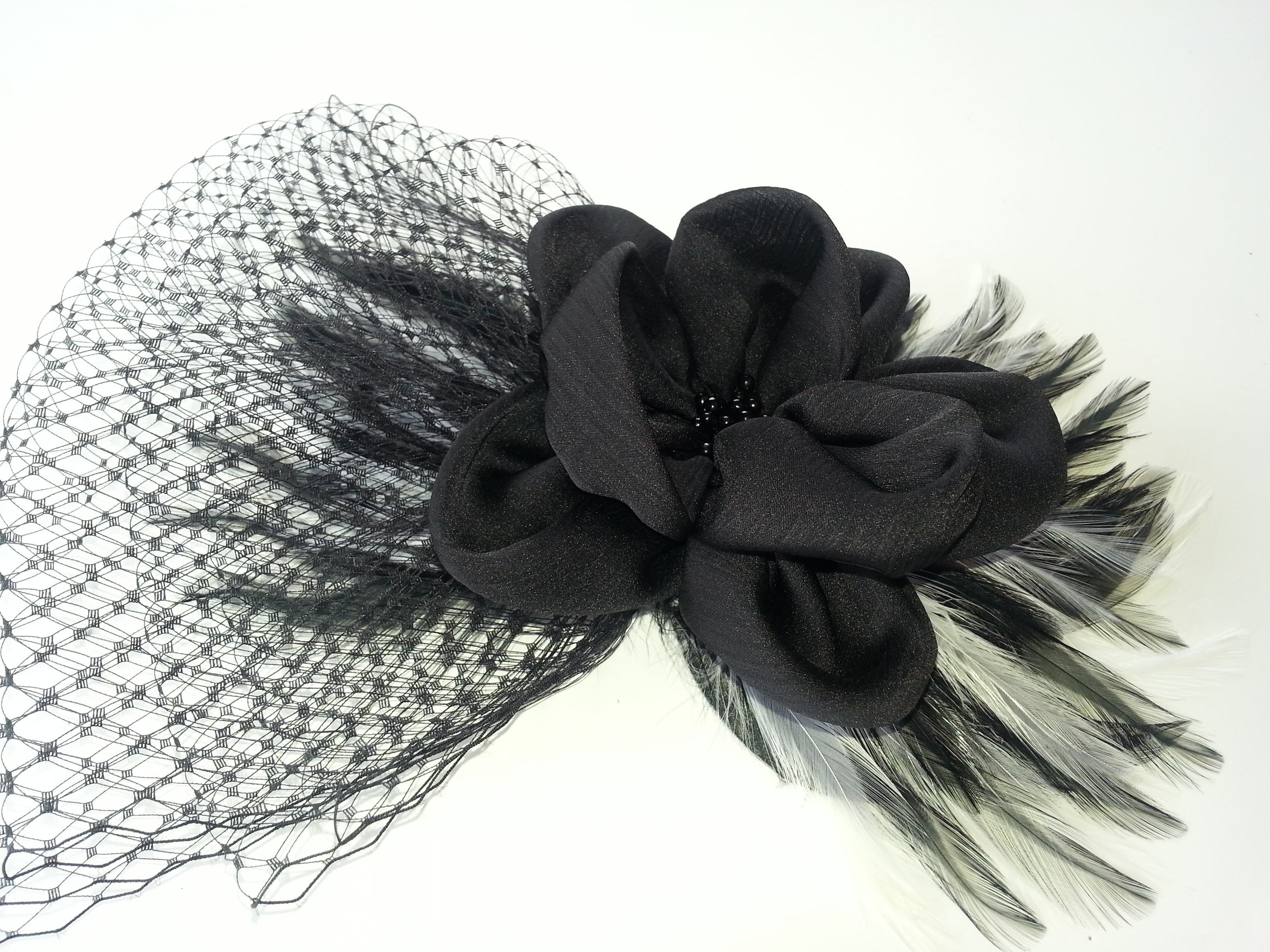 Clip flower pin through the center of the tulle and feathers.