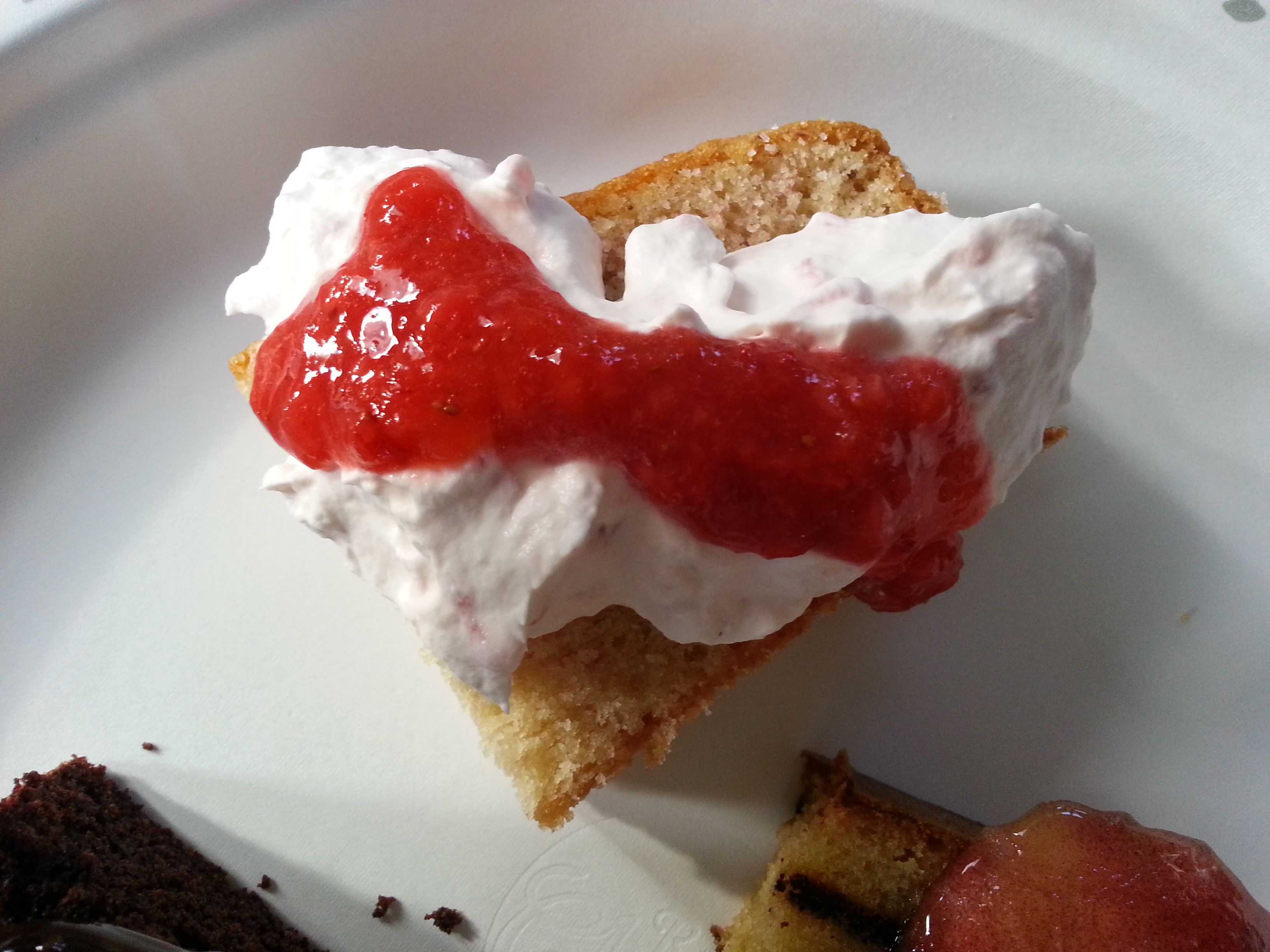 A slice of Fresh Strawberry Cake with Strawberry Whipped Cream and Strawberry Puree.