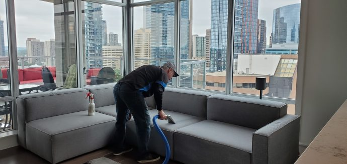 Man cleans upholstery on sectional.