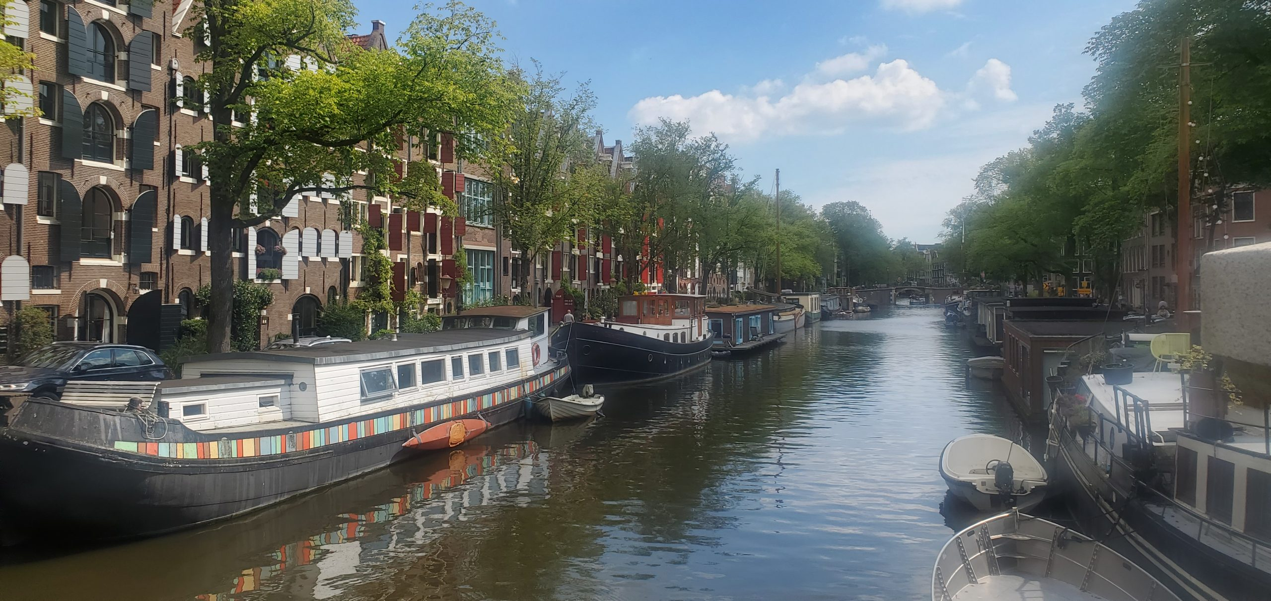 Quaint houseboats line a canal in Amsterdam.